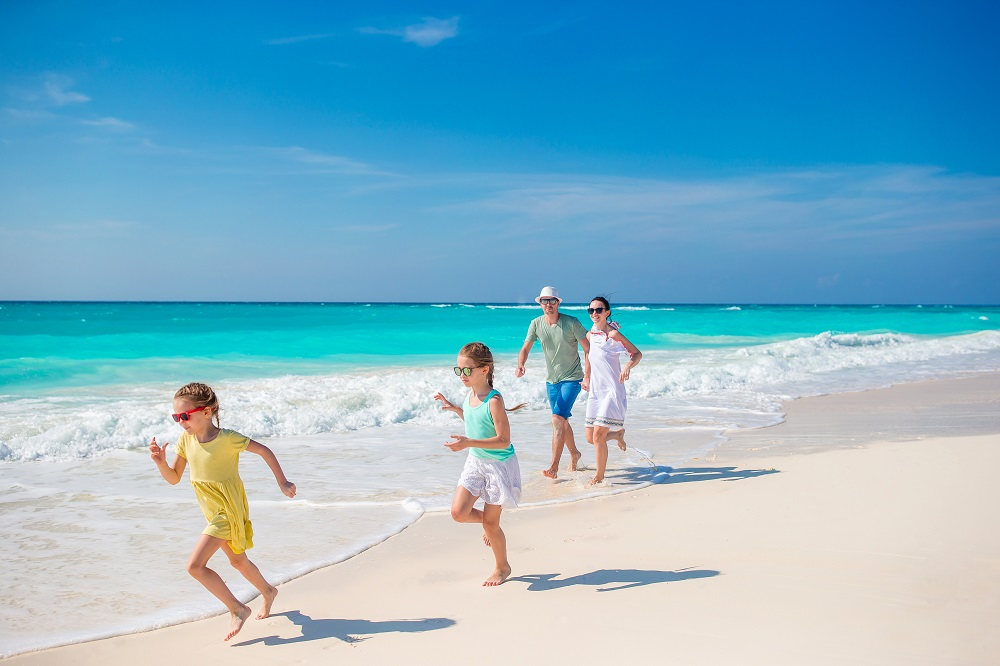 Family on beach is happy after using top 10 travel tips to make their vacation memorable