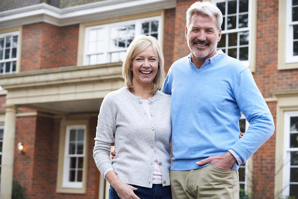 Couple standing outside home are happy they considered four good reasons to refinance now