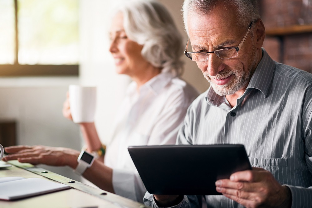 Couple in kitchen use iPad to check their Roth IRAs