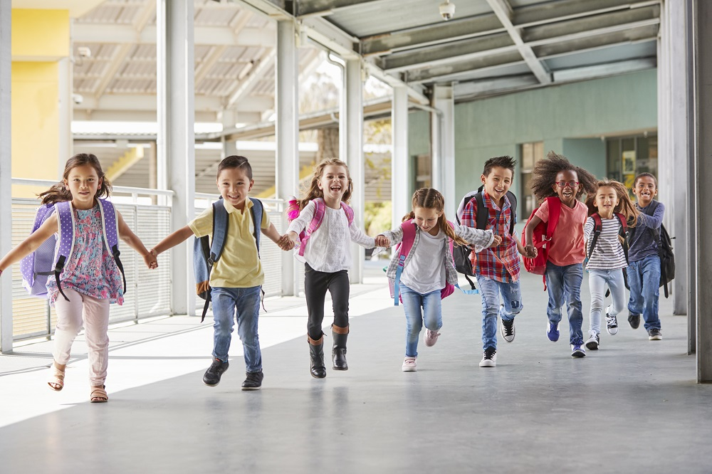 Kids running down school hallway, excited to learn about back-to-school kids' financial literacy checklist