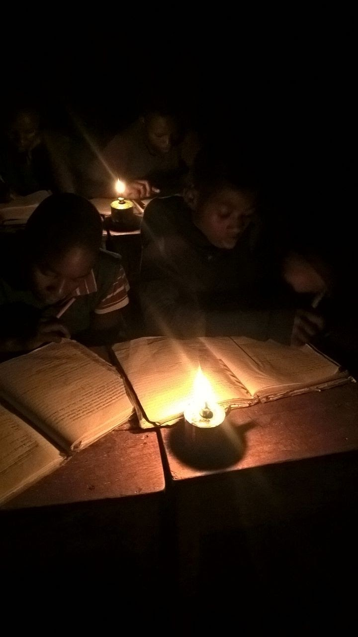 Kids in Senegal study by candlelight