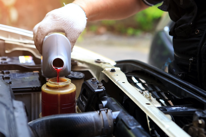 A hand filling car power steering fluid