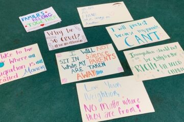 """Posters on a carpet with immigrant supportive messages such as """"love your neighbor no matter where they are from"""""""