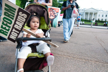 Toddler holding immigration protest sign sitting in stroller