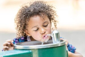 Young child drinking from fountain.