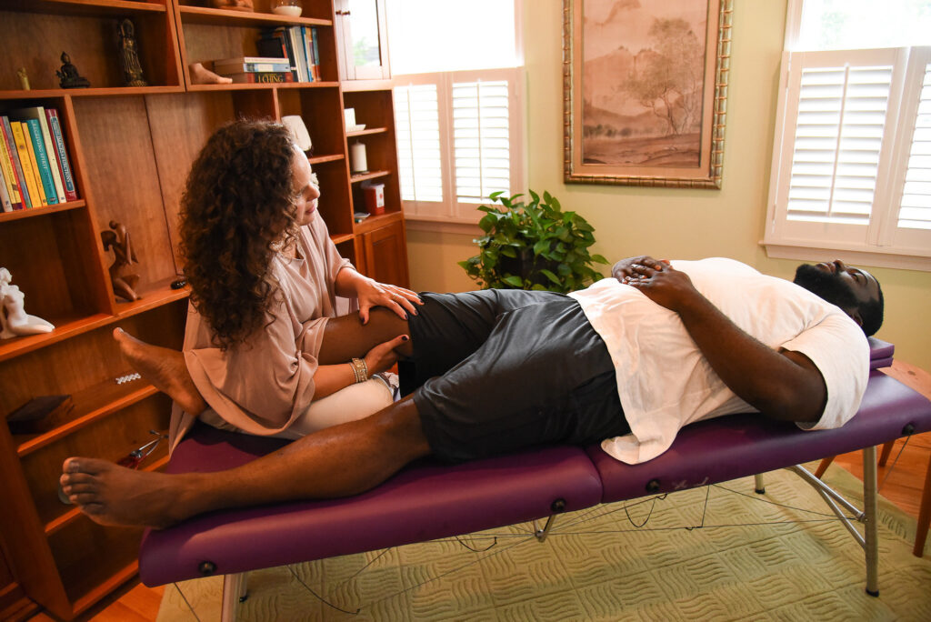 Dark haired woman massaging a client's leg as they lay on a table