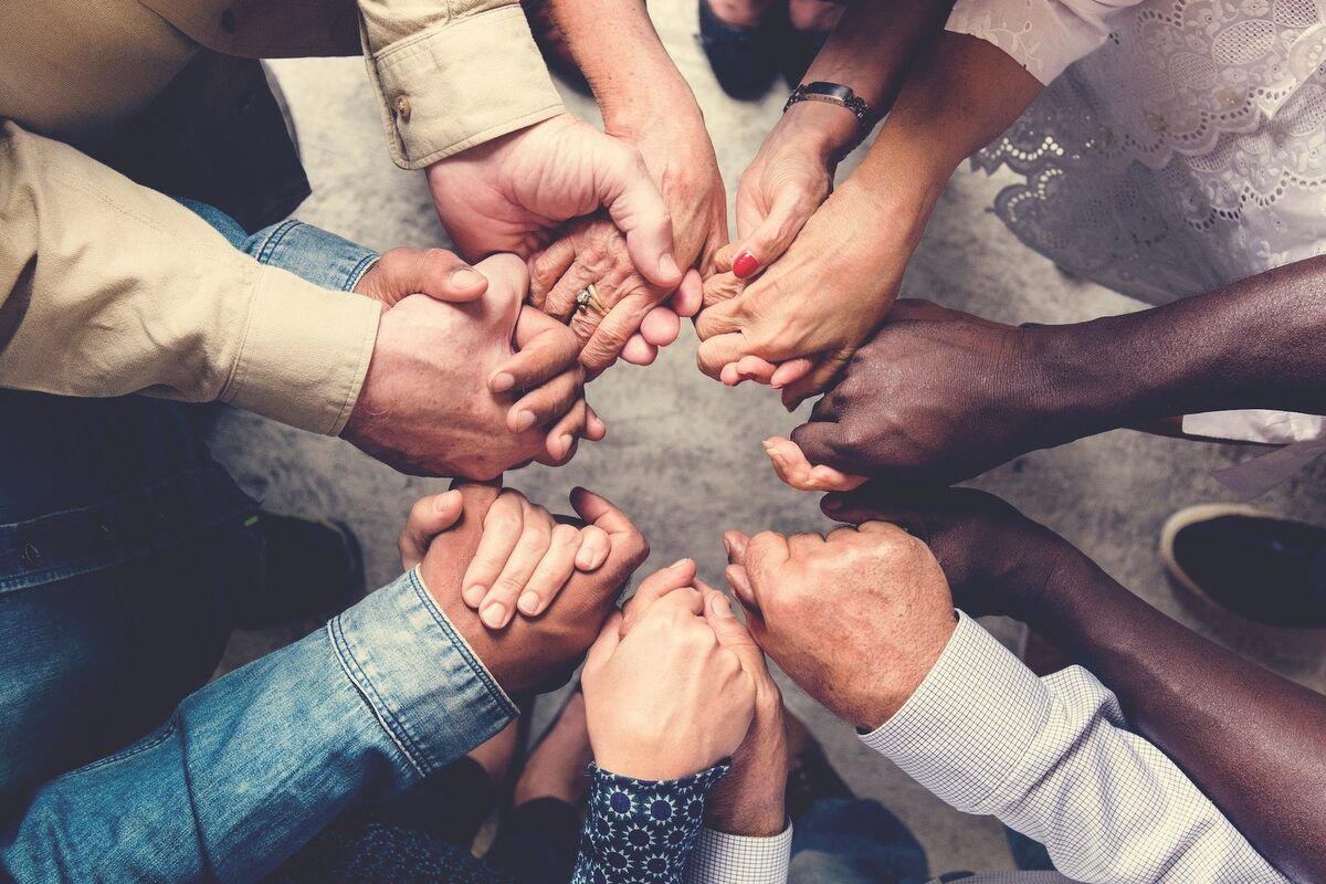 Group of people holding hands in prayer