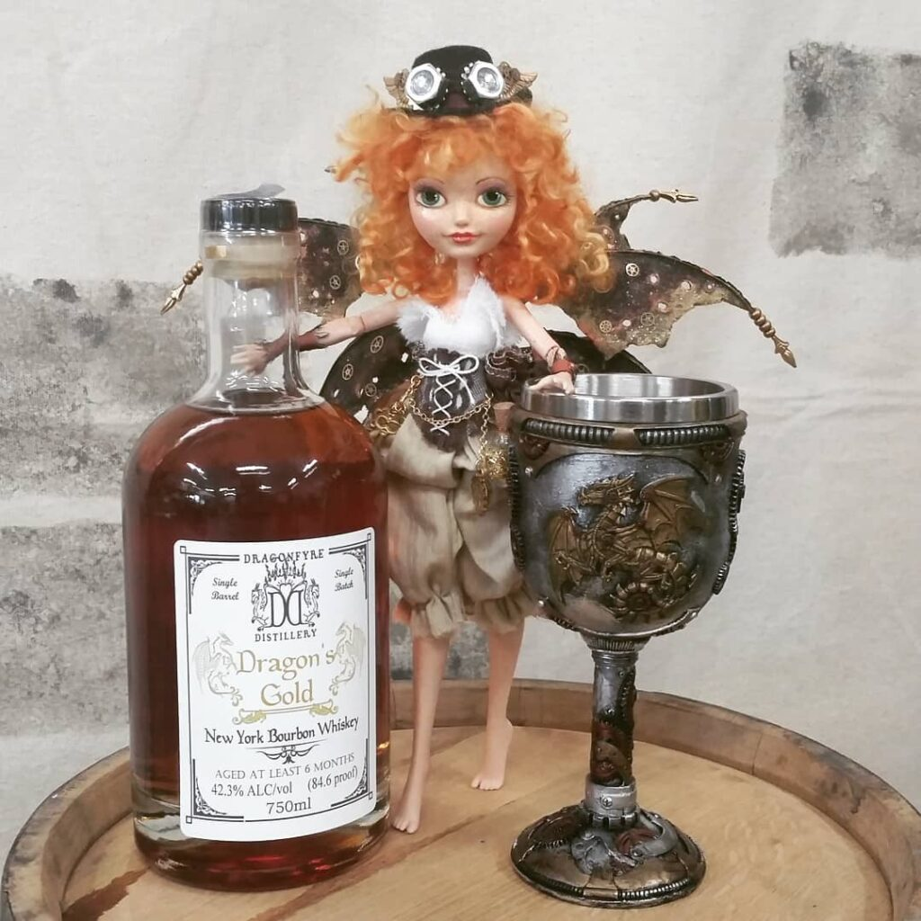 Sylvie the Steampunk Fairy with a bottle of Dragons gold bourbon whiskey and a Steampunk chalice.