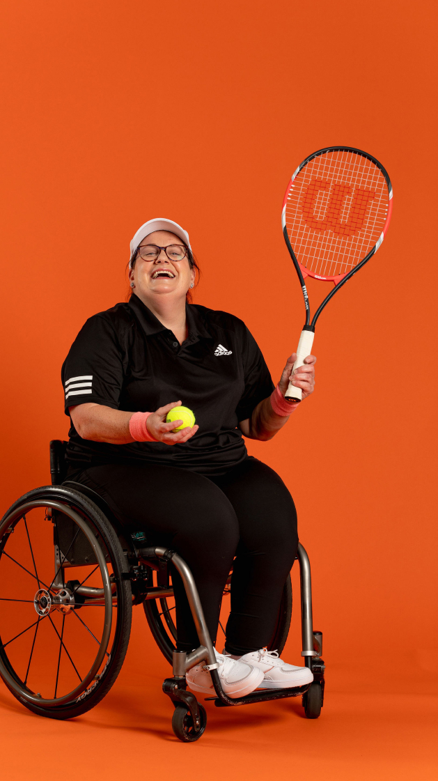 Emily laughing while playing wheelchair tennis