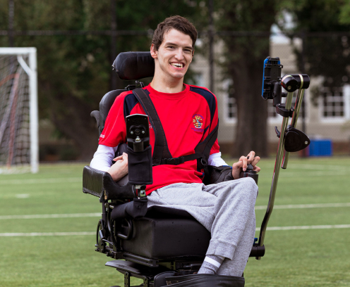 Noah looking happy on the soccer field in his wheelchair