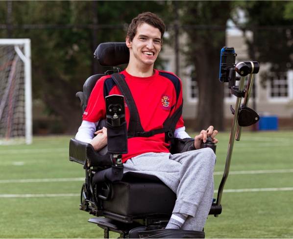 Noah, World's best goalie smiling on the soccer field in his mobility chair