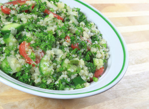 Quinoa Tabouleh salad in a bowl sitting on a wooden table.