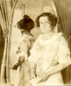 historical photo of a woman standing in front of a mirror looking toward the camera