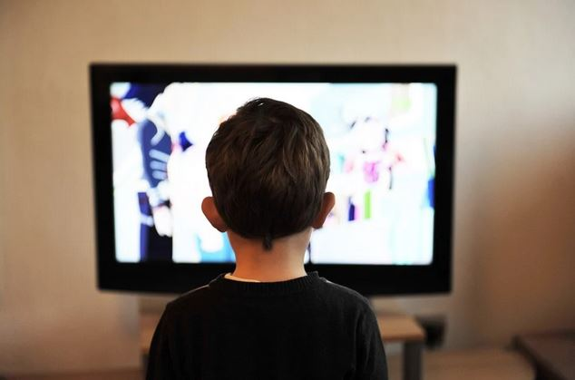 Little Boy Sitting In Front Of TV