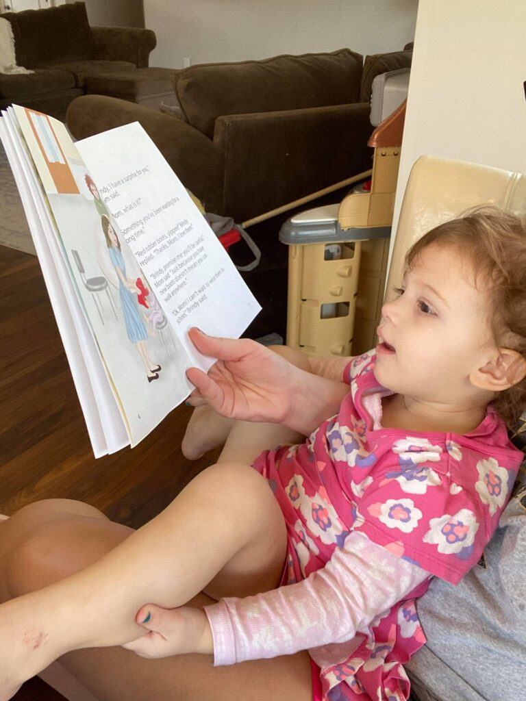 Avery reading Brindy and the Red Rubber Boots Children's Book
