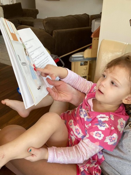 Little girl reading Brindy and the Red Rubber Boots book.