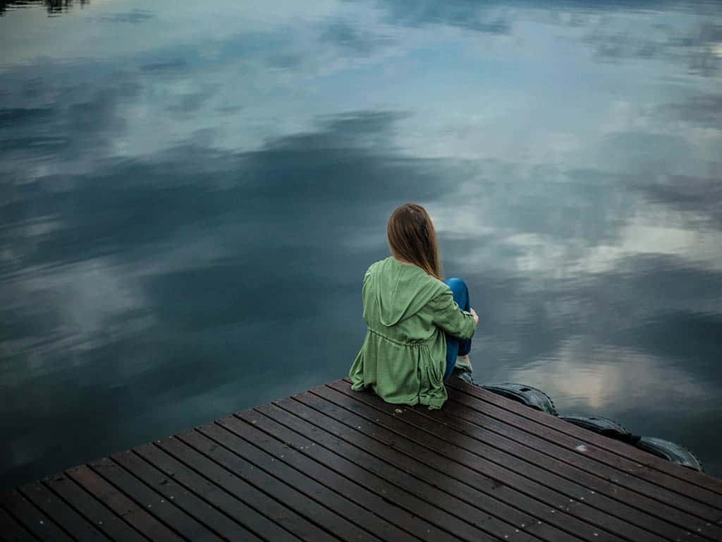 woman deal with anxiety depression sad water reflection