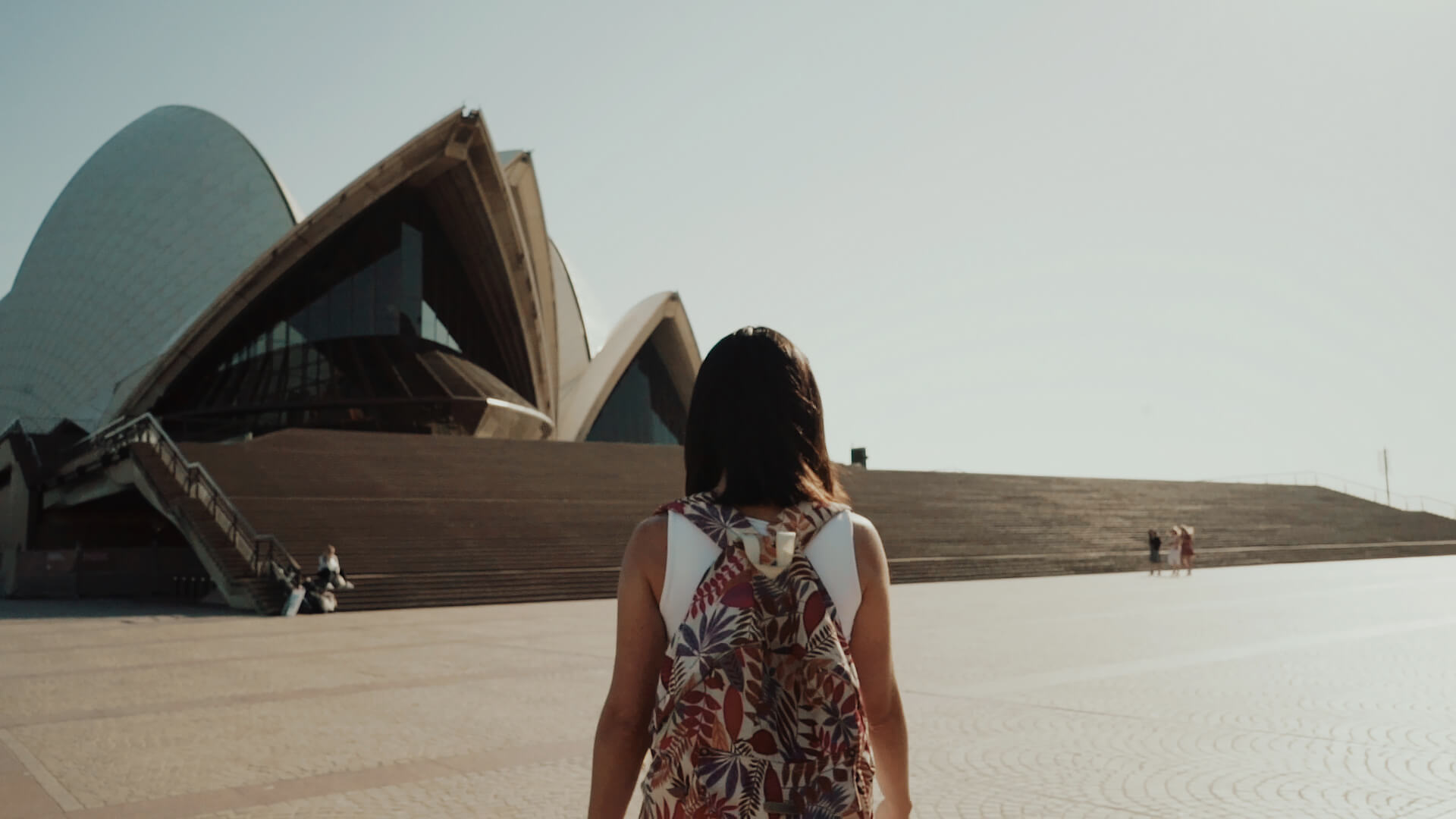 still frame from creative promotional film: student walking at the Opera House