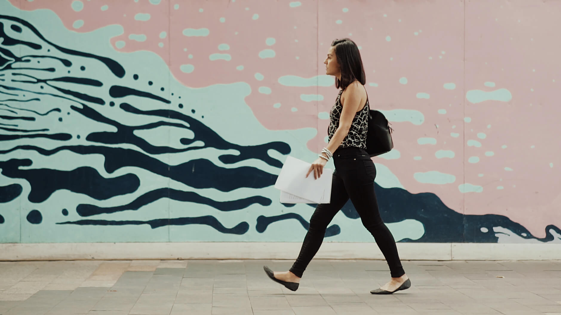 still frame from creative promotional film: women walking on streets with resumes on her hands