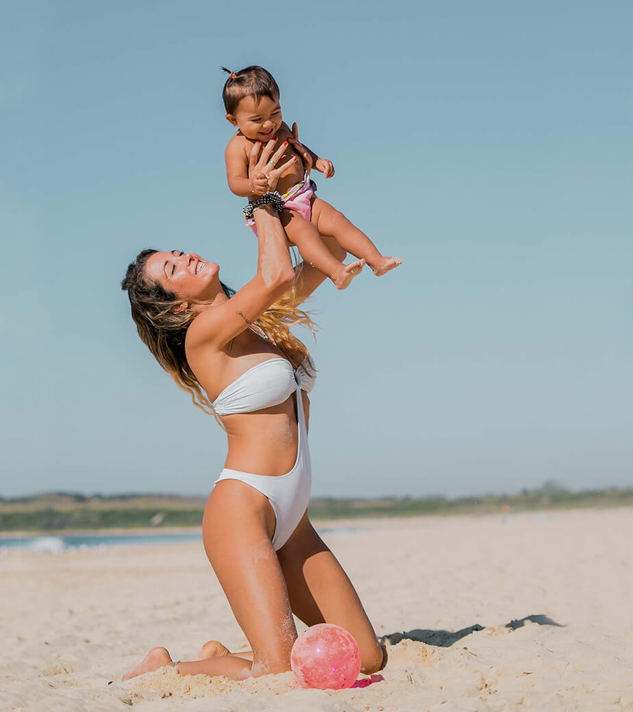family films and photos: mum at the beach holding baby up