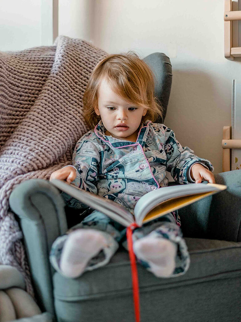 family films and photos: 2 year girl wearing pyjamas sitting in her small couch and reading a book