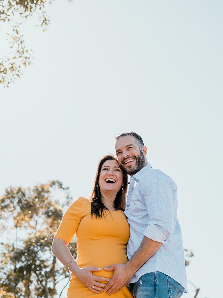 maternity films and photos: couple waiting for a baby looking forward in a beautiful sunny day