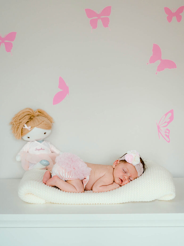 newborn films and photos: baby girl wearing pink pants and sleeping with belly down