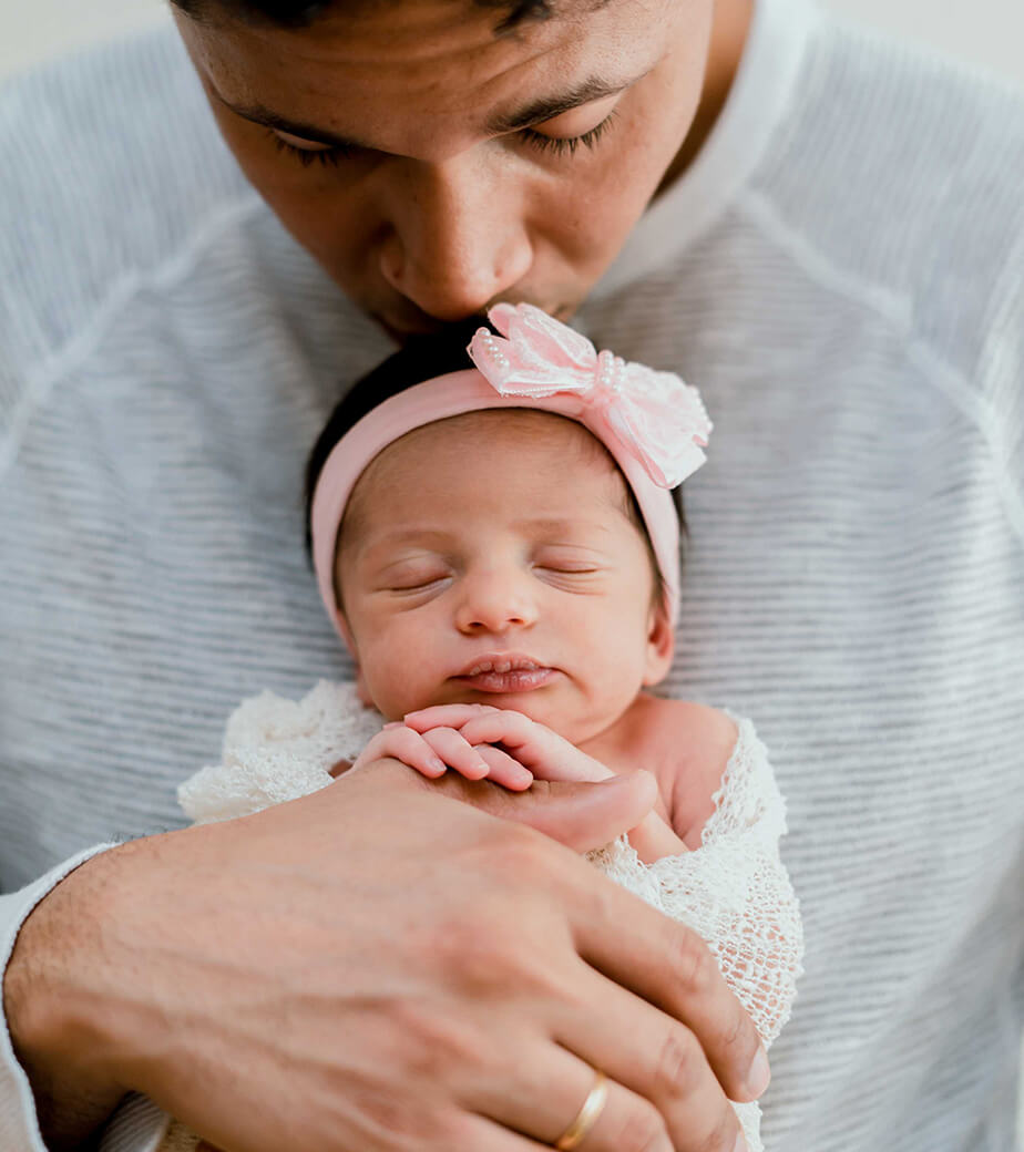 newborn films and photos: daddy holding sleeping newborn and kissing her head