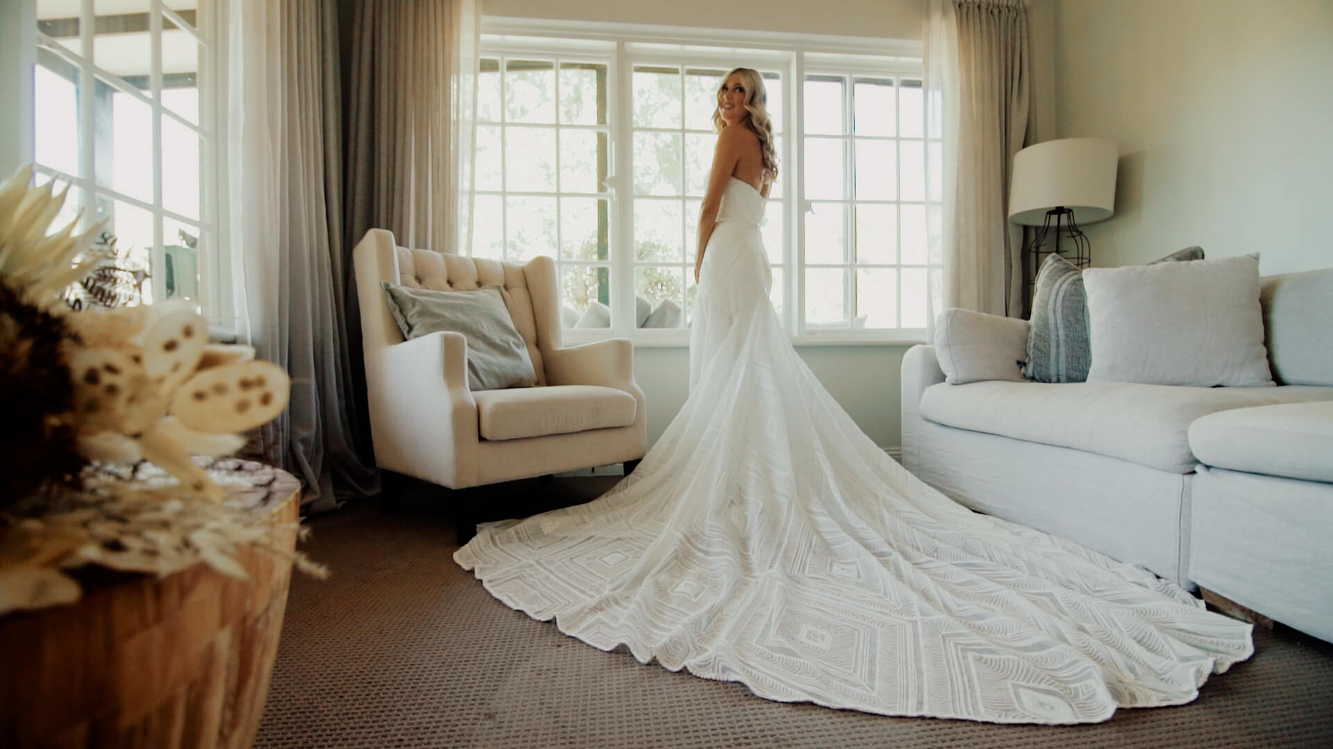 wedding film still frame: bride standing in front of a window revealing full wedding dress
