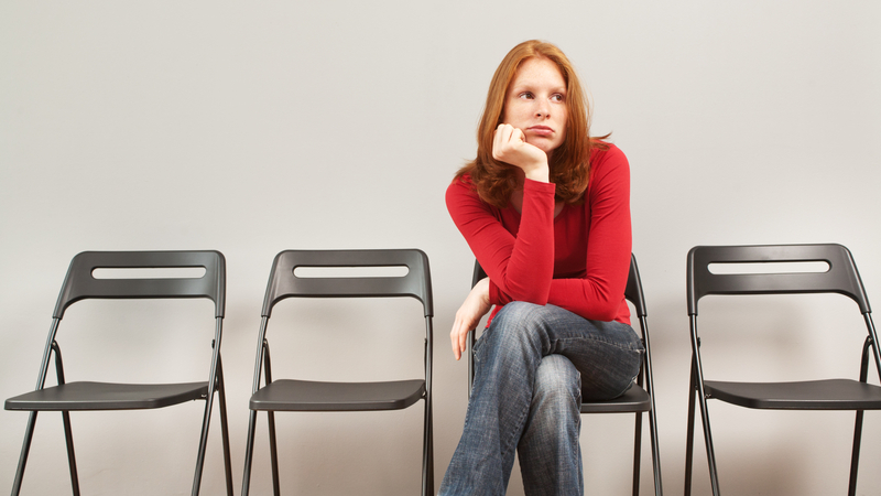 Woman Waiting Next to Empty Chairs