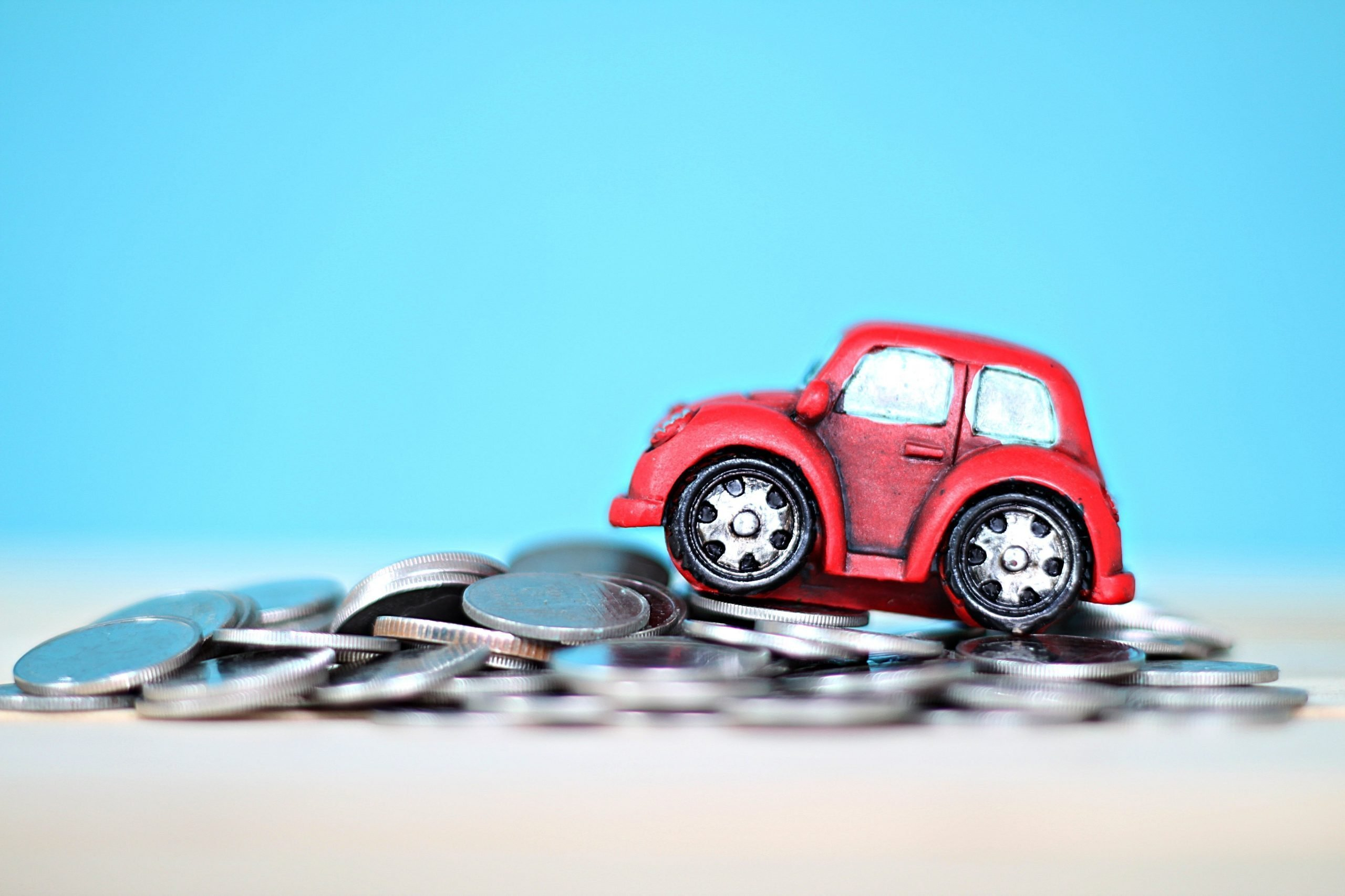 Miniature car model and coins on desk table