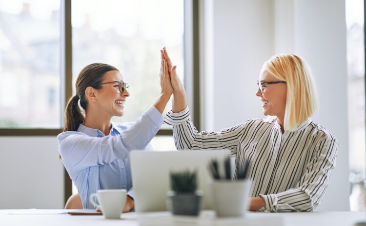 Two smiling businesswomen high fiving together in an office