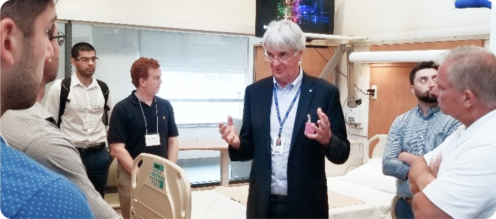 Dr. Geoff Fernie talking to a group of diverse people about his hospital room simulator