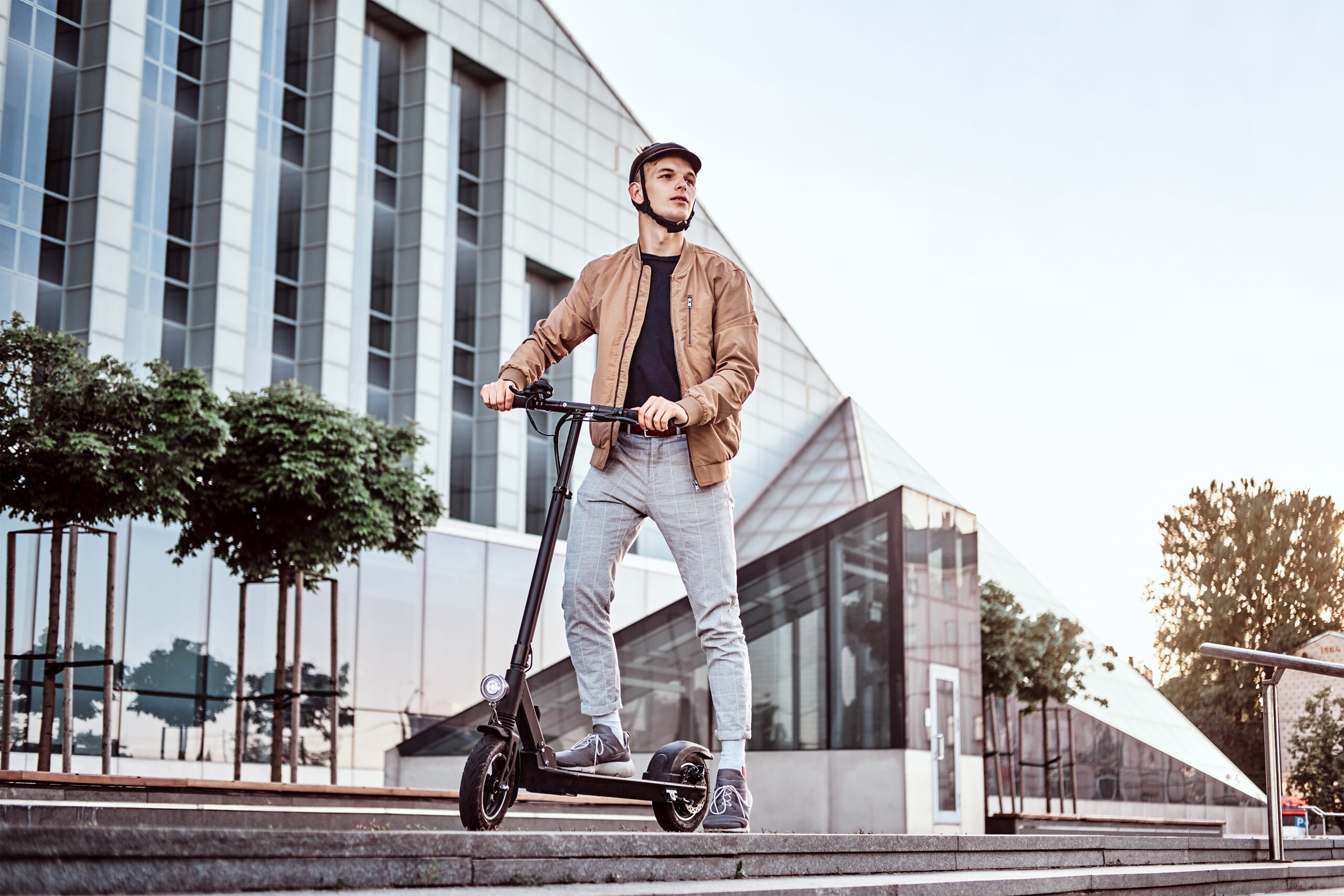 Young man driving an electric scooter and wearing a helmet