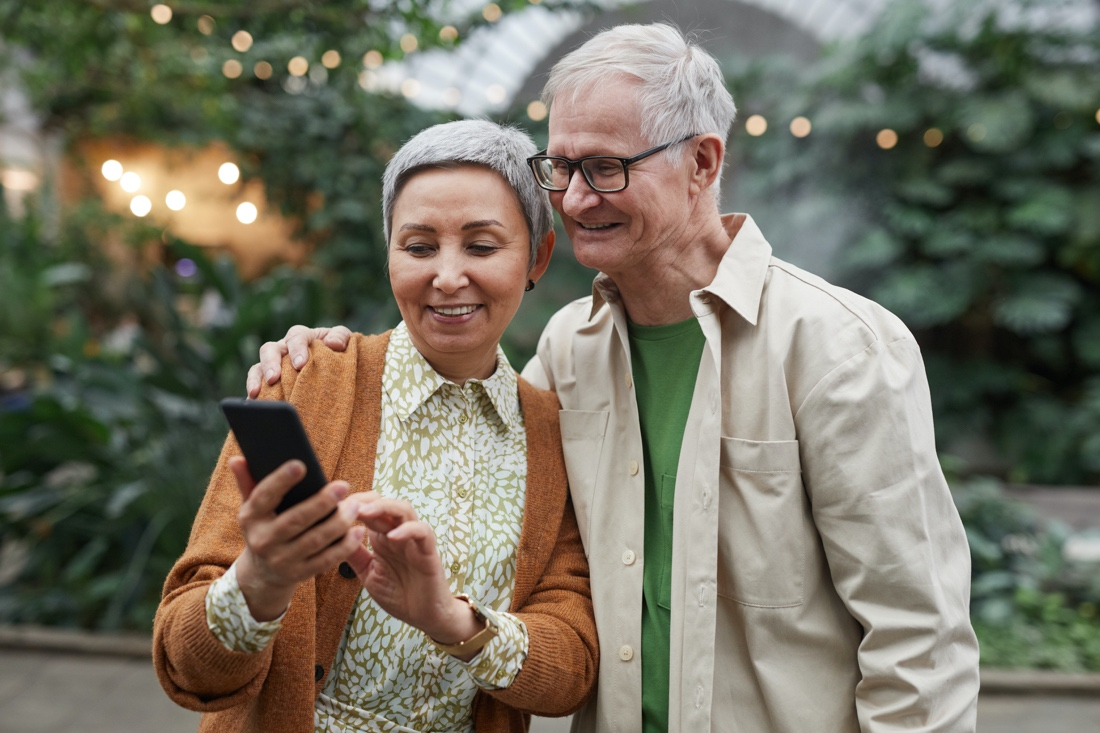 Elderly couple smiling and looking at smartphone