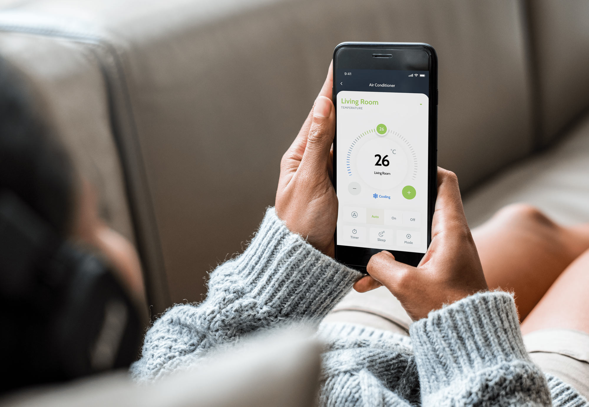 Woman laying down on couch and looking at her smartphone with thermostat screen