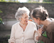 Elderly woman holding hands with younger woman