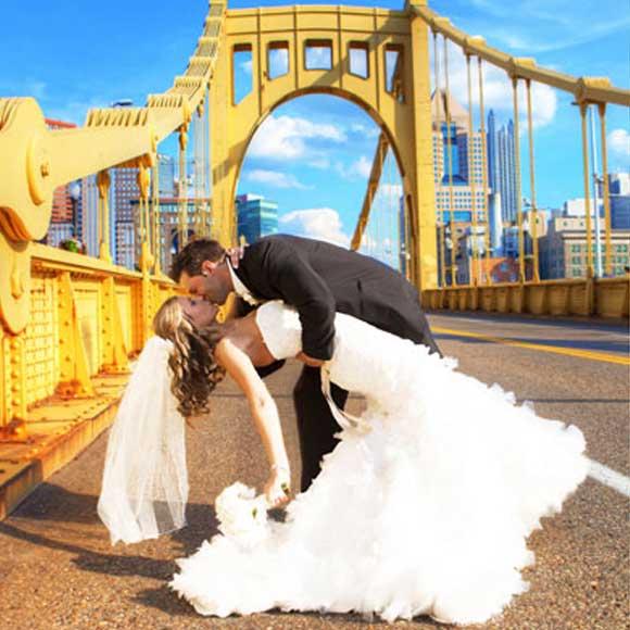 Groom kissing bride on street by bridge