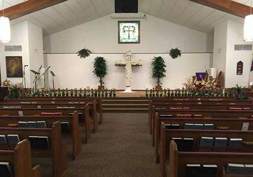 Facing the altar between pews on main aisle of church