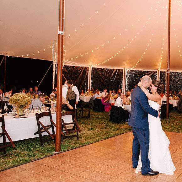 Couple dances under tent for outdoor night wedding