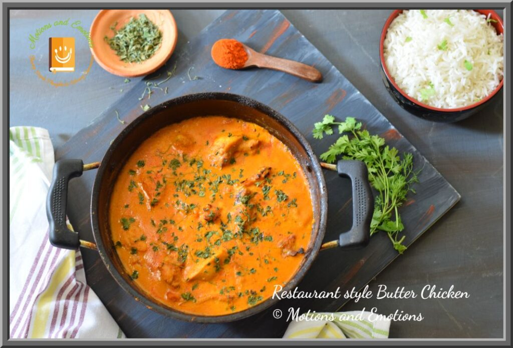 Top view of Butter Chicken in a wok along with rice bowl and spices