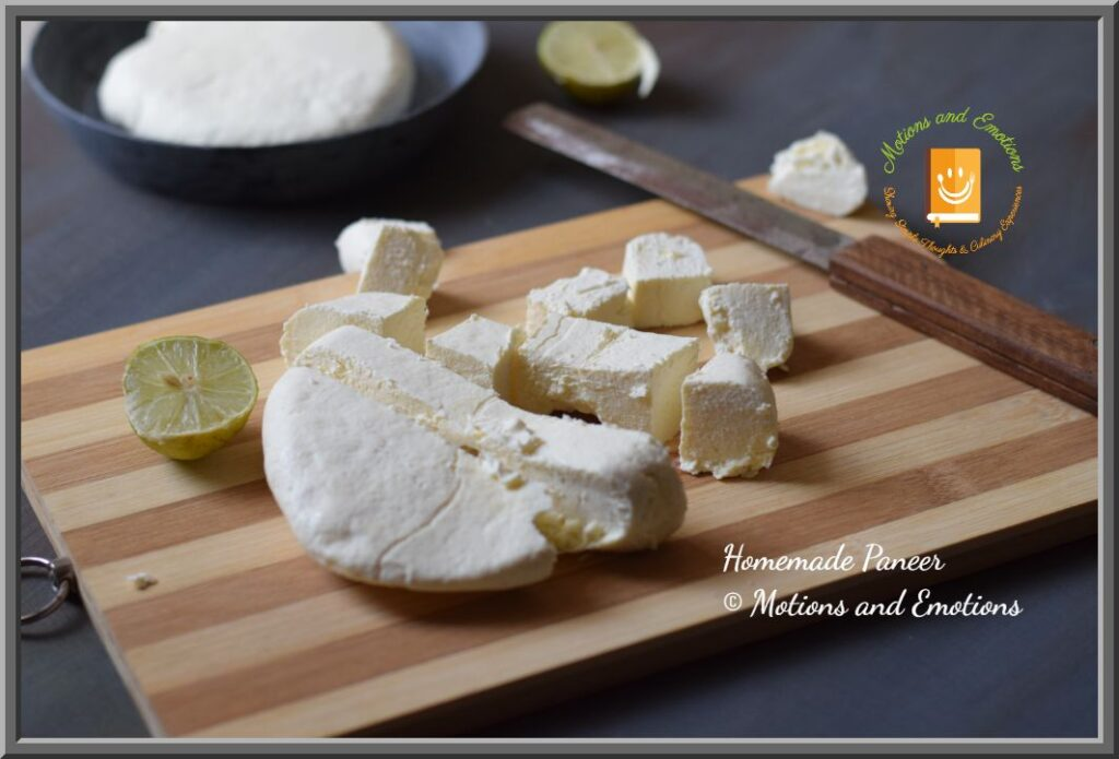 Paneer cubes cut from paneer block scattered on wooden board along with knife and lemon