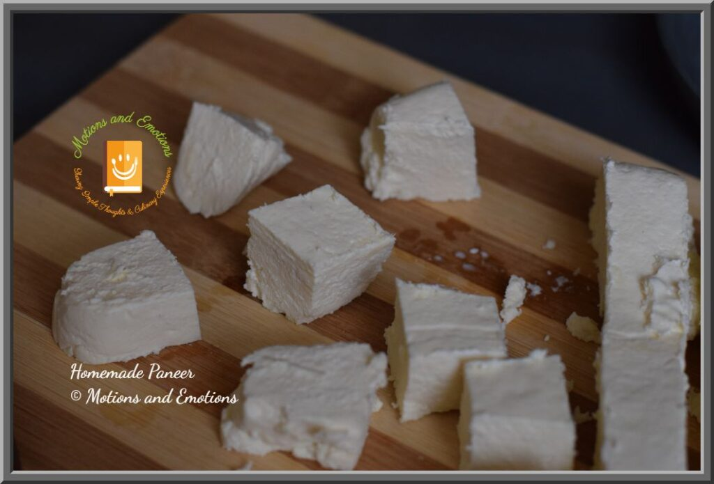 Paneer cubes scattered on wooden board