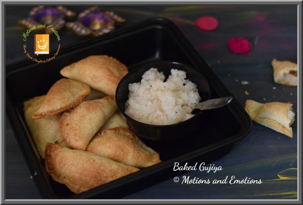 Baked Gujiya in black baking tray along with coconut stuffing in a black bowl with spoon and one broken gujiya