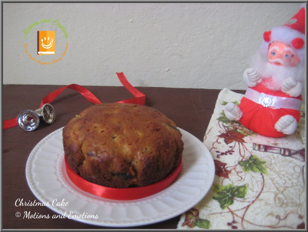Christmas cake on a white plate along with Christmas decorations