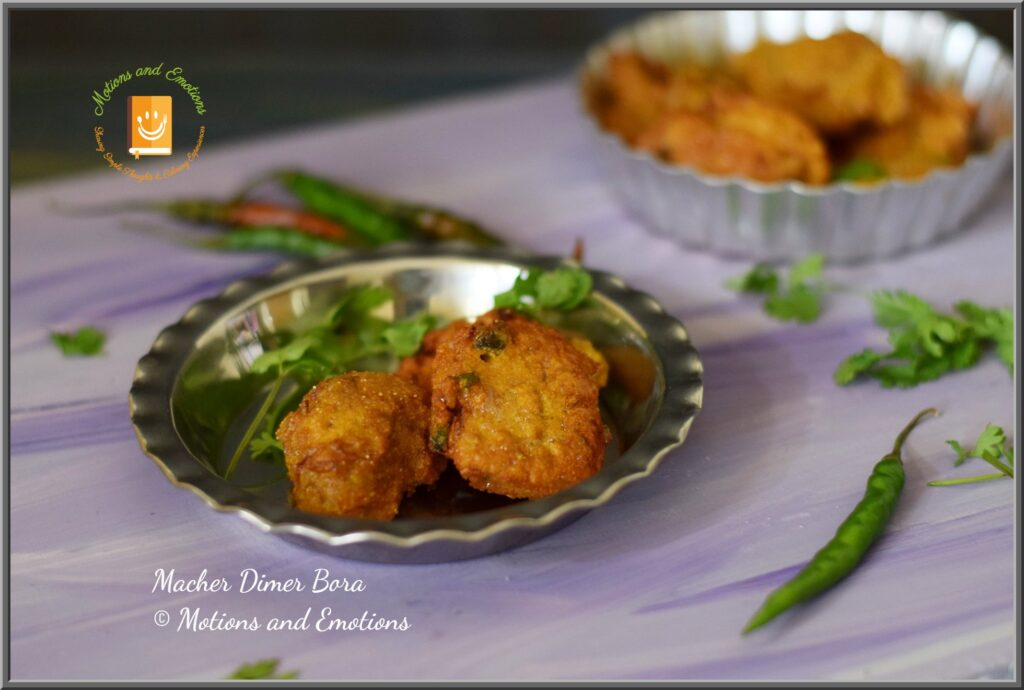 Fish roe fritters served on a steel plate along with green chilli and coriander leaves