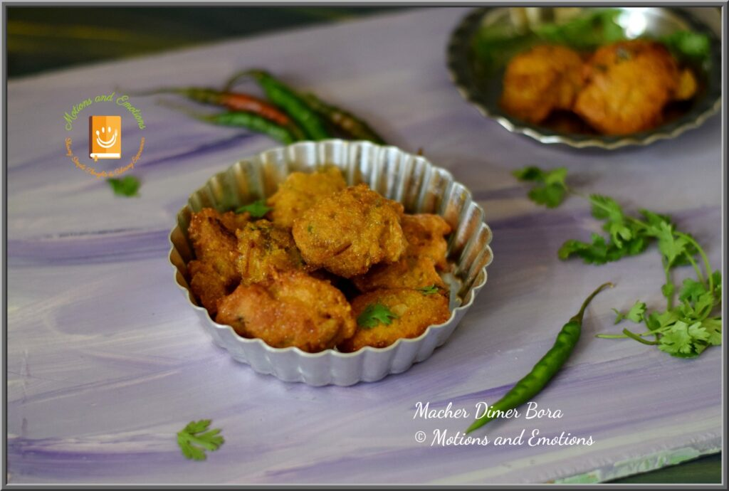 Fish roe fritters served on a pie plate along with green chilli and coriander leaves
