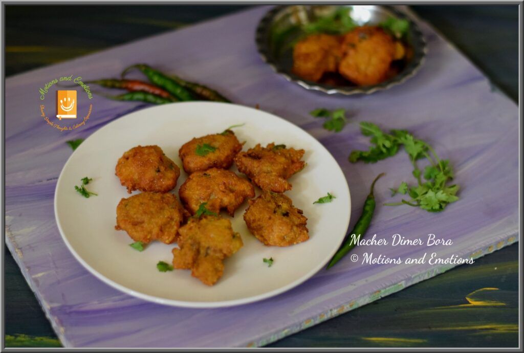 Fish roe fritters served on a white half plate along with green chilli and coriander leaves for garnishing