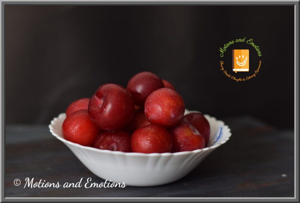 Red plums stacked in a white ceramic bowl