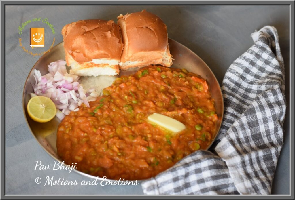 Pav Bhaji served on a steel plate with a dollop of butter , chopped onion and lemon wedge